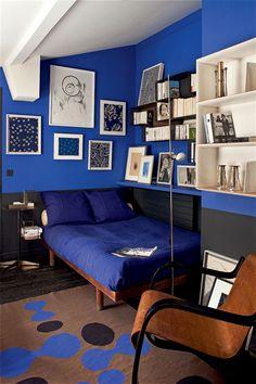 Une chambre 3 ambiances autour du lit de Charlotte Perriand et des étagères de Mathieu Matégot - appartement parisien / boutique de l'antiquaire et décoratrice d'intérieur Florence Lopez - étagère bleue au dessus du lit / bas du mur noir, comme le parquet