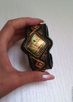 Купить или заказать Браслет с лабрадоритом ВАРИАНТЫ в интернет-магазине на Ярмарке Мастеров. Еще один браслет с нежно любимым мною лабрадоритом. Невероятной красоты камень играет переливами цвета от розовато-золотистых до глубоких сине-чернильных оттенков! Браслет достаточно лаконичный, но очень эффектный! В работе использован качественный японский бисер золотых, бронзовых, синих и черных оттенков. Изнанка натуральная кожа. Украшение достаточно универсальное, вполне подойдет как для…