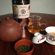 Osmanthus oolong tea presented with gongfu implements: terracotta pot, glass decanter, and gaiwan. Loose tea and tea tin for context