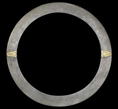 A Sikh gold koftgari watered-steel Quoit  Northern India, 19th Century of circular form with sharpened outer edge, the finely watered steel blade decorated in gold inlay with two stylised palmette motifs to either side