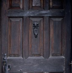 Close shot of the fielded panels of the oak front door and cast-iron door knocker at Hill Top House, the home of Beatrix Potter in Near Sawrey, Cumbria, England, UK.