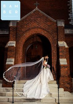 Newlyweds Eric + Shelly sharing a smooch! Shelly si wearing her customized Lea-Ann Beltler Jemma bridal gown (customized with an extra long train) and a gorgeous lace-edged cathedral length veil. Photo by Bamber Photography