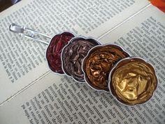 Diseño de Pasadores Nespresso. Colección Remolino.  Realizado con cápsulas nespresso de tonos ocres (dorado, rojizo, cobre y marrón) con forma de florecilla y pasador metálico.   Bisutería, Accesorios y Complementos de Diseño. Fabricado de manera totalmente artesanal y 100% hecho a mano, lo que le confiere a cada complemento un carácter único y personal.  http://lacrisalidadelamariposa.wordpress.com/2014/03/27/pasador-nespresso-artesanal-02/