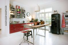 Red cabinet kitchen: i love the red cabinets and black fridge in this kitchen