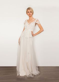 5299b7412bfc5 Brigitte-Curlicues of beaded French lace embroider the open neckline and  delicate flutter sleeves of this tulle gown. Reappliquéd lace and a soft  organza ...