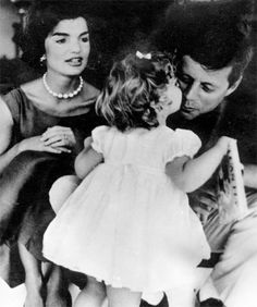 Caroline Kennedy pictured in 1959 kissing her father John F Kennedy as her mother Jackie looks on
