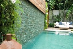 the pool highlighted by wall coated in bluish stones ,and wood panel.