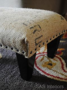 Burlap Sack Ottoman - using old $5 garage sale ottoman, coffee sack, and upholstery nails (i knew I was saving those coffee bags for something!)
