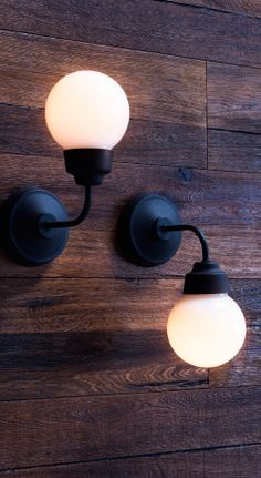 Two bathroom lights, one facing up, the other facing down, on wood-panelled wall.