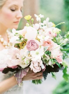 Loosely constructed bouquet of primarily white flowers with touches of blush pink.