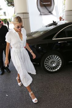 Hailey Baldwin looking gorgeous in an all white outfit (shirtdress, platform peep toe heels) in Cannes