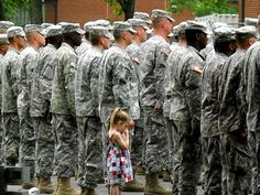 A family photo that shows a little girl beside her father and his fellow soldiers in uniform as they prepare to go to war.