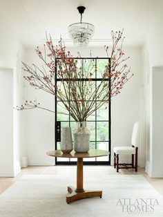 Home Decorating ideas - Round entry table in light filled white entry with drop crystal chandelier and extra large branch floral arrangement | Mix and Chic: A beautifully restored Art Deco residence in Atlanta.