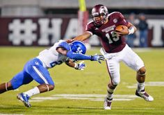 Mississippi State quarterback Dak Prescott (15) fights off a tackle attempt by Kentucky safety Eric Dixon (28) as he runs for long yards. (Rogelio V. Solis/AP)
