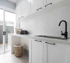 SPLASHBACK A white textured overlay to bring the hamptons to life in the laundry. Also admire the matte black tapware and handles for a a bold yet beautiful contrast.