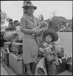 """May 8, 1942 - Ibuki Hibi, 5, holds her doll and waits with her mother, Hisako Hibi, 35, as they stand with the family's luggage in downtown Hayward, California. The Hibi family was being taken to the Tanforan Assembly Center. When they arrived at Tanforan they lived in a horse stall. Ibuki said, """" We saw big piles of hay in the room and thought it is for the horse to eat, but was told it was to stuff a mattress for sleeping.""""  Dorothea Lange photo"""