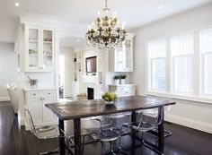 An eat-in kitchen features a crystal chandelier illuminating a rustic dining table lined with Ikea ghost chairs, Ikea Tobias Chairs. Ikea Dining Table, Tufted Dining Chairs, White Dining Table, Dining Decor, Rustic Table, Vintage Table, Wood Table, Rustic Living Room Furniture, Living Room Paint
