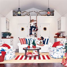 Classic holiday colors look fabulous next to punchy nautical hues. Kick the festive atmosphere up a notch with candy red throw pillows, a red-striped rug, and adorable miniature potted Christmas trees.