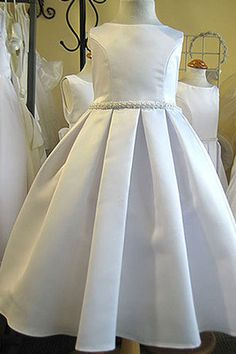 Classical elegant unique box pleated skirt, made with first quality bridal satin. All hand made pearl trim on the waist and A tulle underskirt adds fullness with a satin sash that ties in the back. #cradlelinensboutique #flowergirldress #boxpleatedflowergirldress #girlformaldresses  www.cradlelinens.com
