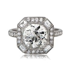 A Magnificent Old European Cut Diamond Engagement Ring. The center diamond is surrounded by a halo of 16 Old Mine diamonds and 4 baguette cut diamonds.