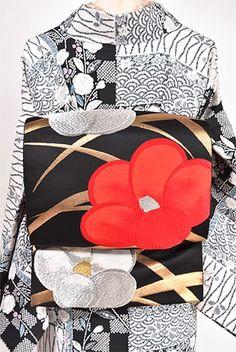 黒地に典雅な気品ただよう金の糸で織りだされた優美な弧を描く芝草に、梅のような椿のような白銀と紅の大輪の花が重ねられた大正浪漫・昭和レトロな華やぎ香る名古屋帯です。
