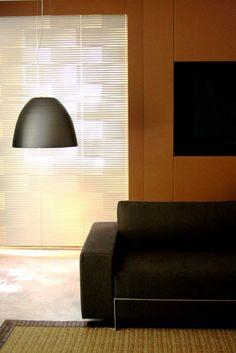 Lançamento da Luxaflex, a persiana de alumínio tem recortes que formam desenhos contra a luz. Posicionados em frente às janelas, os pendentes (La Lampe) completam o visual geométrico.