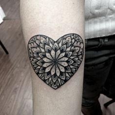 Pequeño tatuaje de un mandala con forma de corazón en el antebrazo, tatuaje diseñado por el artista Kirk Nilsen.