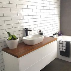 White subway tiles with a grey grout White Bathroom Tiles, White Subway Tiles, Laundry In Bathroom, Bathroom Layout, Bathroom Interior Design, Small Bathroom, White Tiles Black Grout, Wooden Bathroom Vanity, Bathroom Tapware