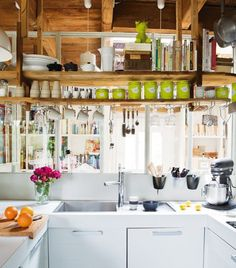 a small kitchen with lots of light thanks to open shelves and views through other rooms