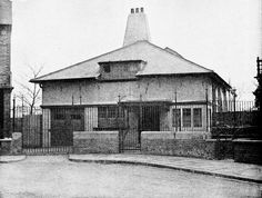 Voysey's house and studio by C. F. A. Voysey. 1891. The building today is almost completely obscured by a high brick wall and vegetation. 17 St Dunstan's Road, London.