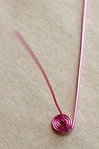 Step 5 to Instruction for Using Jewelry Wire to Wrap an Irregular Gemstone Showing Spiral Made Using WigJig Spiral Maker Tool.