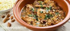 Kippendijen op Marokkaanse wijze uit de tajine of pan met kaneelstokjes en amandel