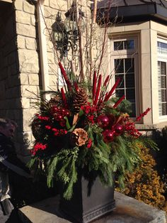 Wow outdoor holiday porch Pot - with red dogwood, red millet, vine balls, birch poles and berries.   Equals awesome.