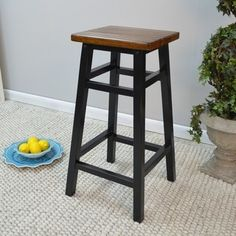 This contemporary bar stool is crafted from select hardwoods and features a grooved oak seat and black antique finished legs. This sleek bar stool will add a stylish accent to your home decor.