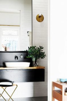 This renovated bathroom has a sleek black vanity with a brass counter top /
