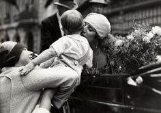 Queen Astrid of Belgium kissing a baby in the streets of Namen, 1929.