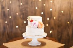 simple 2 layered ruffled cake is adorned with a cascade of ranunculus, peony, garden rose and stock.
