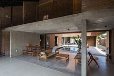 The open plan living and dining room. Tagged: Living Room, Chair, Concrete Floor, Coffee Tables, and Sofa.  Photo 4 of 15 in Light and Shadow Help Shape This Modern Brick House in Vietnam