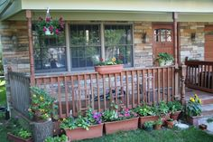 Amazing Front Porch Railings You Should Consider : Attractive Front Porch Decoration With Natural Stone And Brick Wall Combine With Red Brown Wooden Railing Plus Hanging Planter And Beautiful Flowers Garden