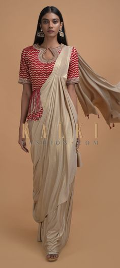 Buy Online from the link below. We ship worldwide (Free Shipping over US$100)  Click Anywhere to Tag Pale Gold Ready Pleated Saree In Shimmer With Fancy Tassel Adorned Red Blouse Online - Kalki Fashion Pale gold ready pleated saree in shimmer lycra trimmed with tassels on the pallu.Paired with a red blouse in brocade silk embellished with gotta patches, zari, cut dana and beads on the neckline.