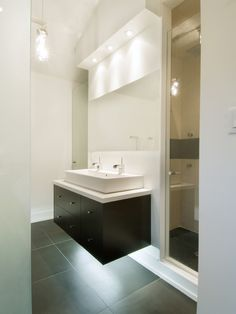 For lighting, we may want to go with a small overhang (as pictured above) with recessed lighting running the length of the bathroom (over vanity and toilet).