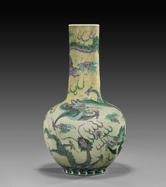 """RARE ANTIQUE FAMILLE JAUNE DRAGON VASE Rare and antique, Chinese Famille Jaune enameled porcelain dragon vase; of well potted bottle form, depicting three-clawed green and light aubergine dragons amid swirling clouds and flaming pearls on a light yellow ground; possibly Kangxi Period; H: 16 1/4""""; Provenance: Exhibited in 1994 at Treasures of China - Longwood Visual Arts"""