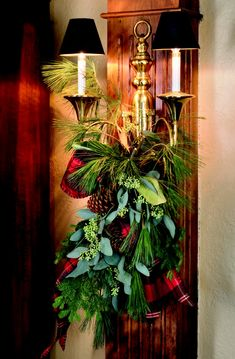 Brass horn sconce with black shades decorated for Christmas with a swag of greenery -- Nell Hill