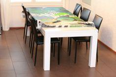 Kiiltovalkoinen pöytä ja mustat nahkaiset tuolit