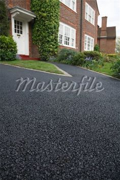 New asphalt tarmacadam driveway outside a beautiful brick house in London. Lots of copy space - Stock Photos : Masterfile