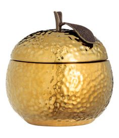 Scented candle in an apple-shaped ceramic holder. Lid with knob and decorative leaf in patterned metal. Diameter 3 1/2 in., height 4 1/4 in. Burn time 10 hours.