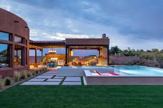 Contemporary Tuscon Outdoor Space With Pool -- The Tuscon, Ariz., home has an amazing outdoor living space that combines the outdoor kitchen and dining room with a sleek, contemporary pool. Large square and rectangle pavers are surrounded by Bermuda grass. Bright red lounge chairs are submerged on the sundeck, creating the perfect spot to relax in the pool.