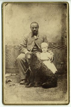Black man with white child and dog - 1890