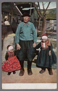 Man poseert met twee jongetjes aan de hand, alledrie in Marker dracht. Marker jongetjes dragen tot ongeveer hun vijfde jaar jurken en geruite borststukken. 1895-1910 #NoordHolland #Marken