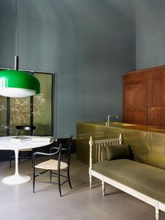 Brass counter / green/grey wall / bright green lamp / Eero Saarinen Tulip marble table / Antique room divider as wall decor